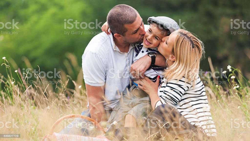 Mother and father kissing their boy stock photo