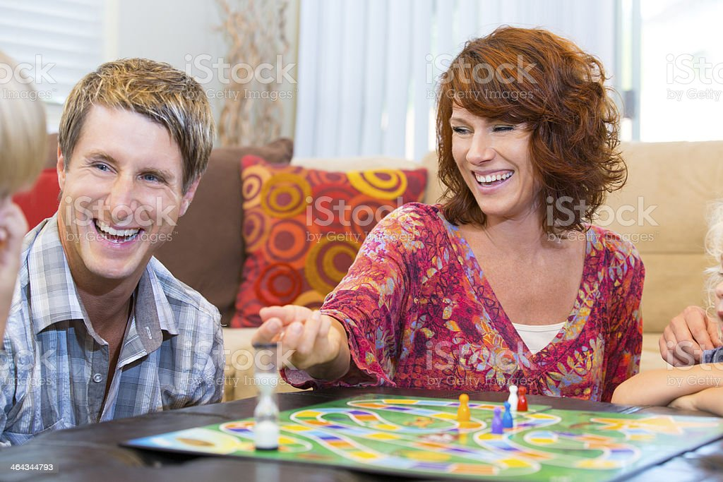 Mother and father laughing playing a board game with kids stock photo