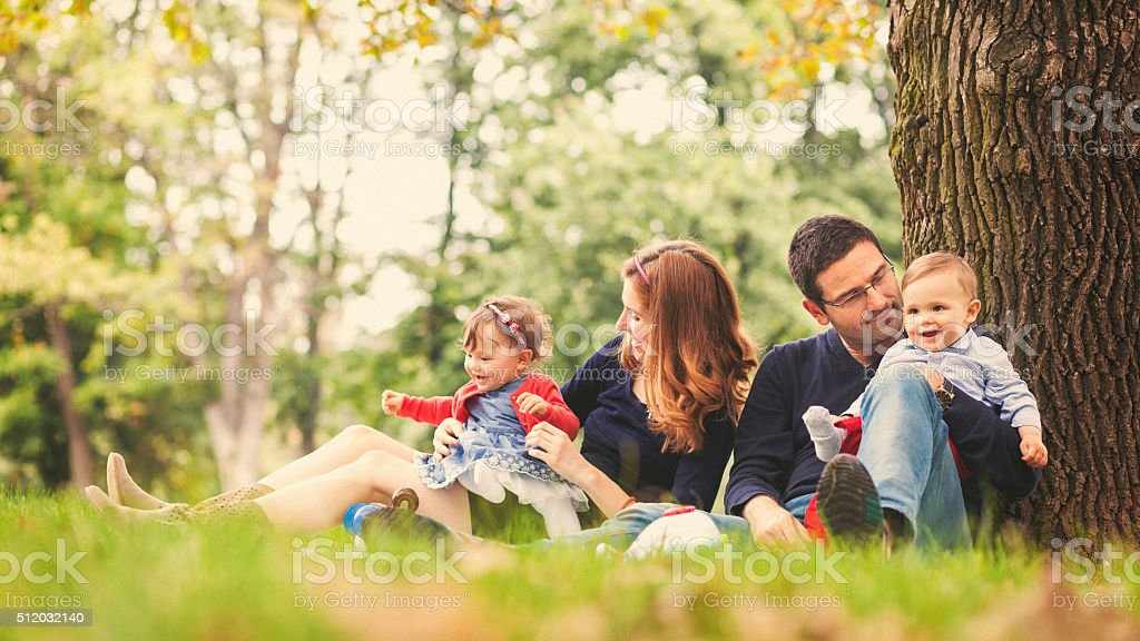 Mother and father with their babies outdoor stock photo