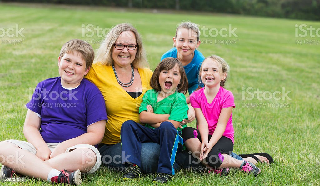 Mother and four children sitting on grass in the park stock photo