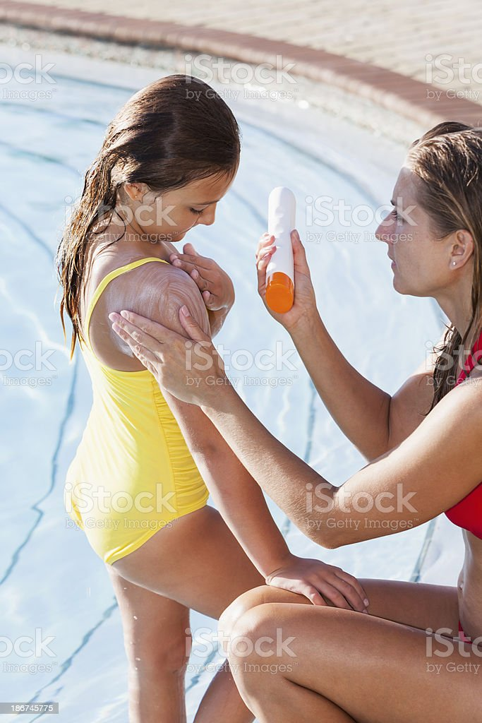 Mother and girl by pool using sunscreen royalty-free stock photo