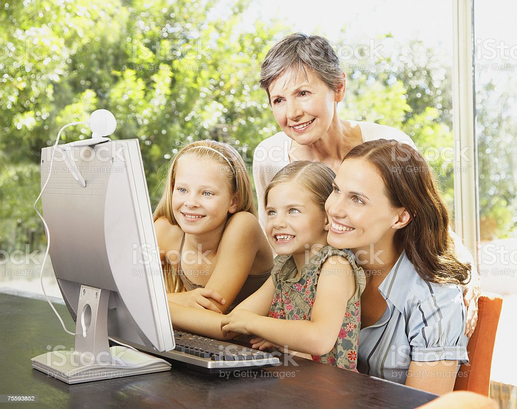 A mother and grandmother using a computer with her two young kids royalty-free stock photo