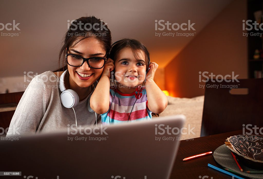 Mother and her baby girl listening to music on laptop. stock photo