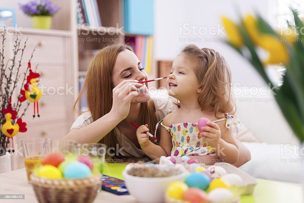 Mother and her baby have fun while painting easter eggs stock photo