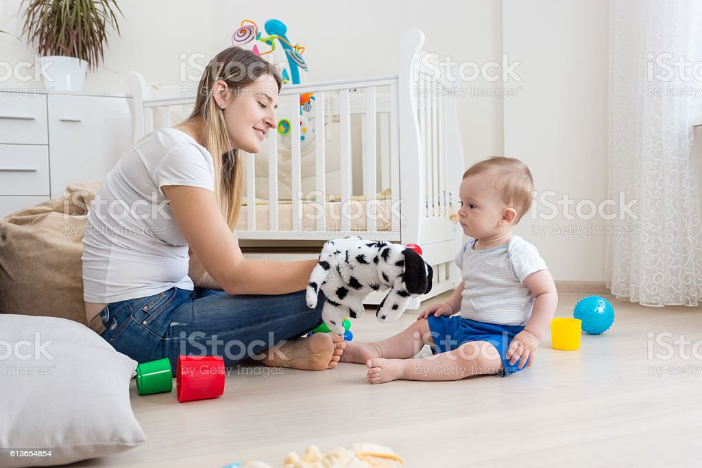 Mother and her baby son playing with puppets stock photo
