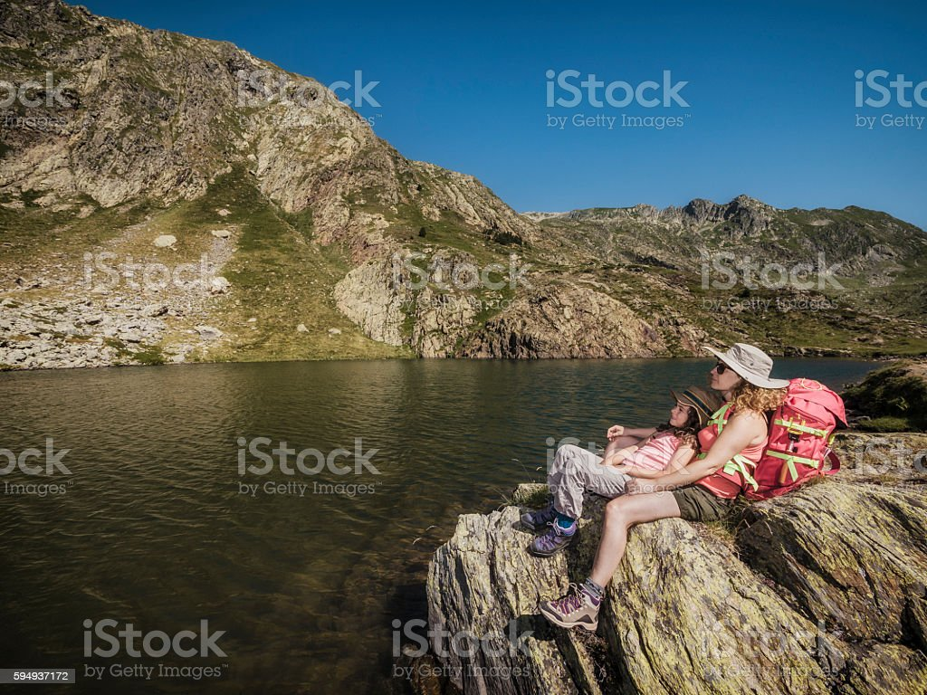 Mother and her child hiking in the mountains stock photo