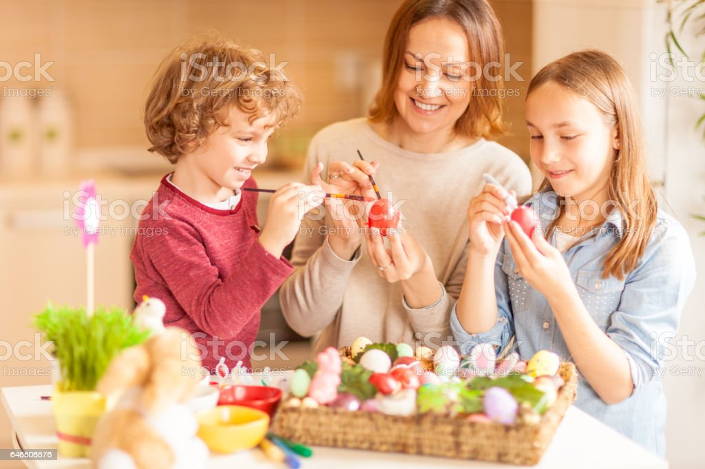 Mother and her children decorating Easter eggs stock photo