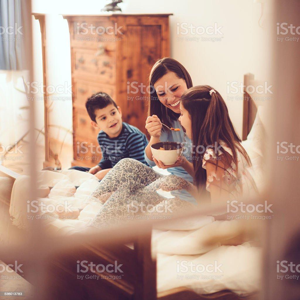 Mother and her children having breakfast in the bedroom stock photo