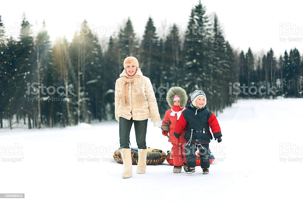A mother and her children walking in the snow royalty-free stock photo