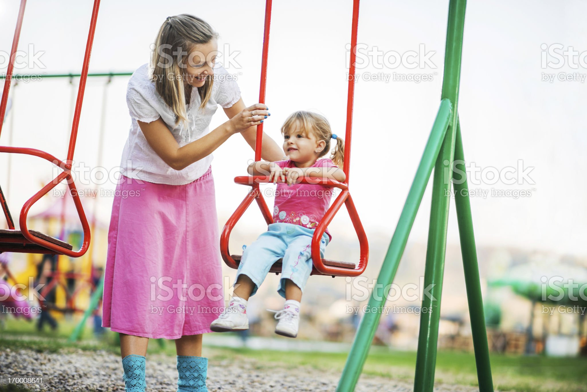 Mother and her cute daughter enjoying outdoors on a swing. royalty-free stock photo