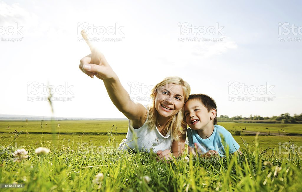 Mother and her cute son lying in the field. royalty-free stock photo