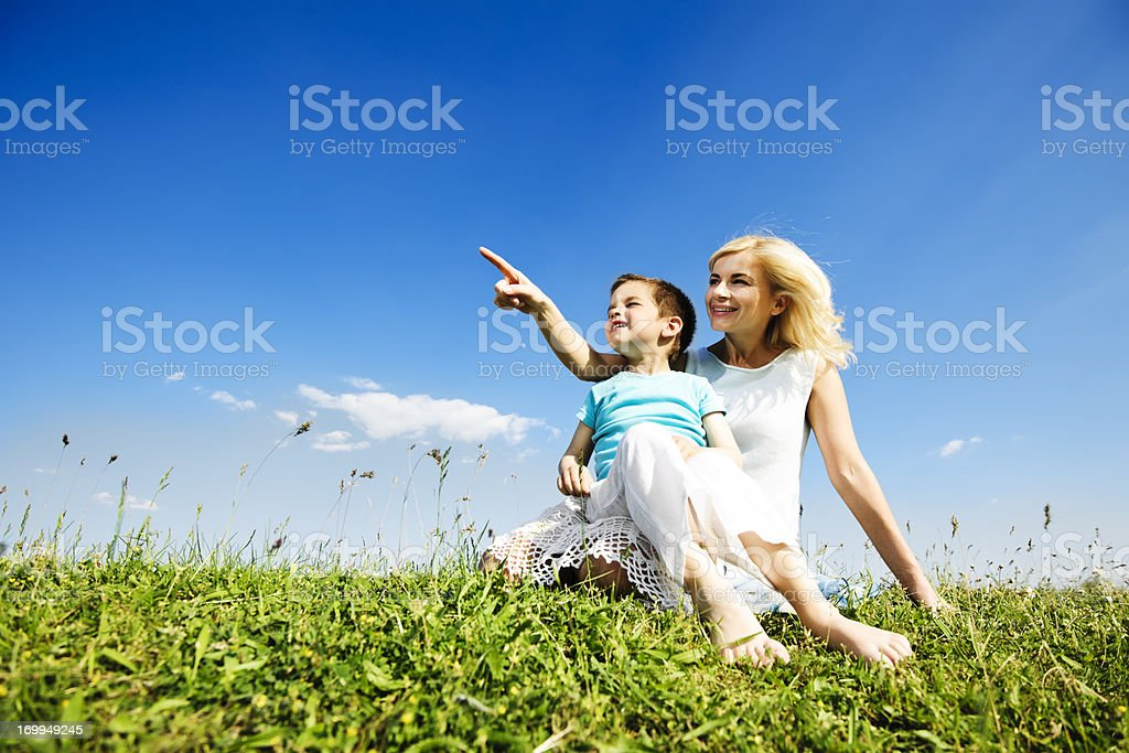 Mother and her cute son sitting in the field. royalty-free stock photo
