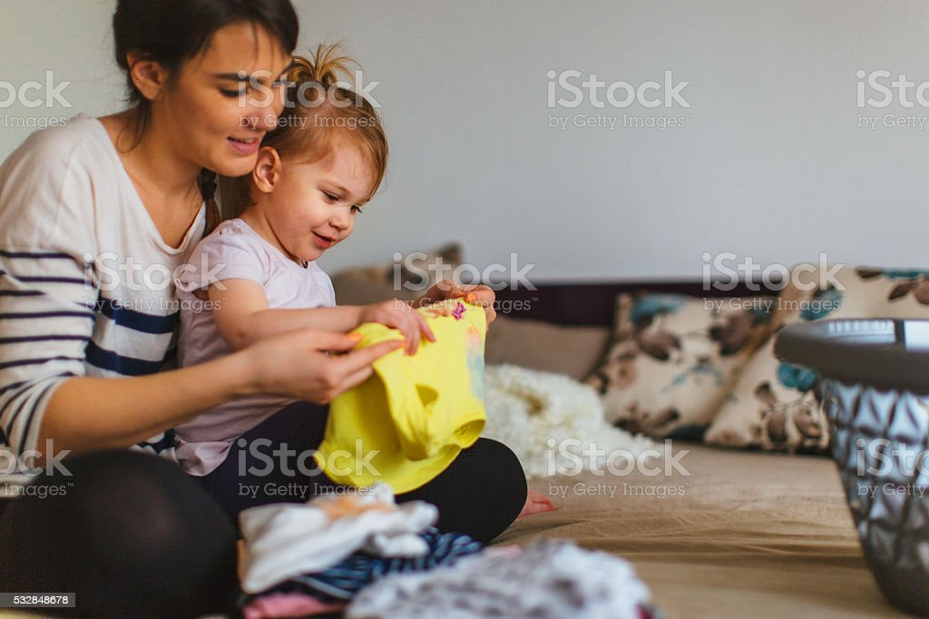 Mother and her daughter folding laundry together stock photo