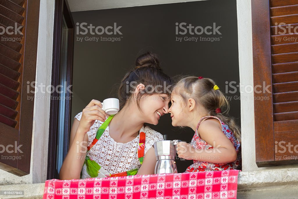 Mother and her daughter holding traditional Italian coffee set stock photo