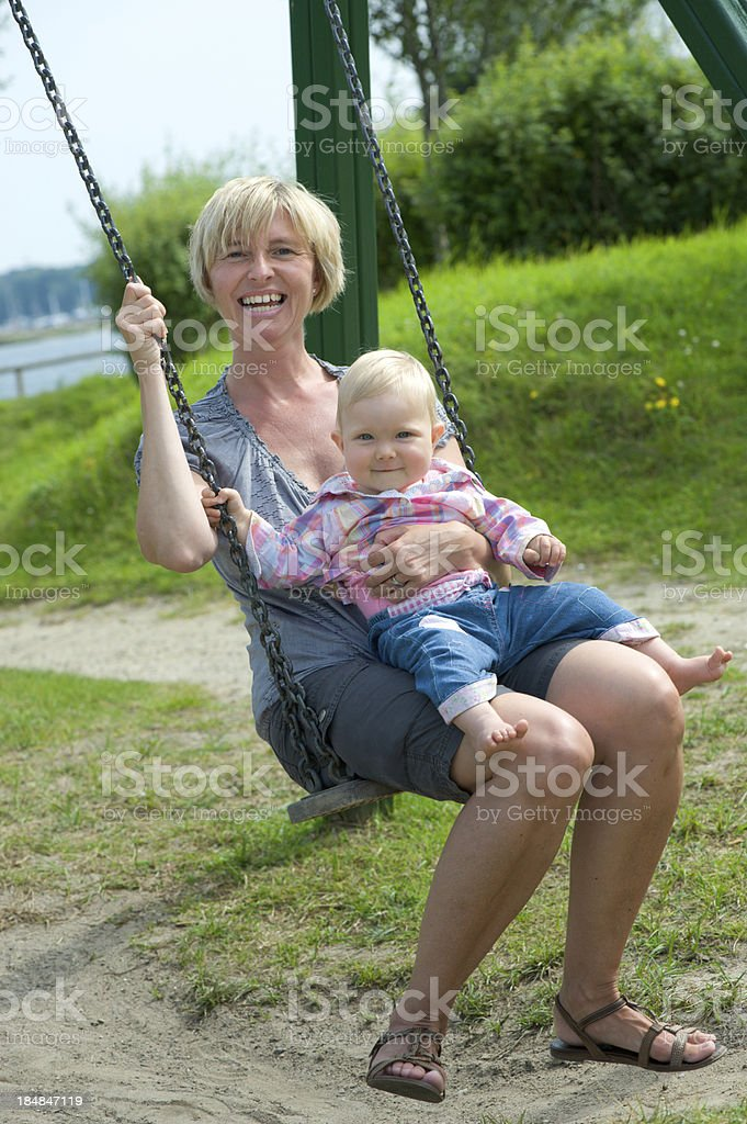 Mother and her daughter on a swing royalty-free stock photo