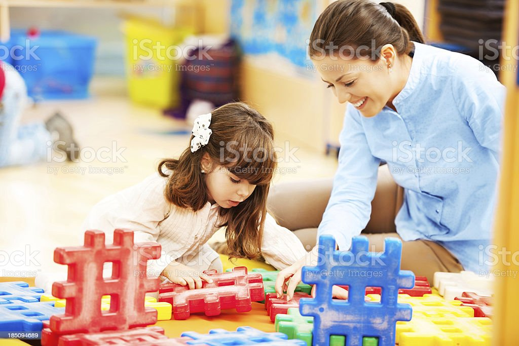 Mother and her daughter stacking blocks royalty-free stock photo