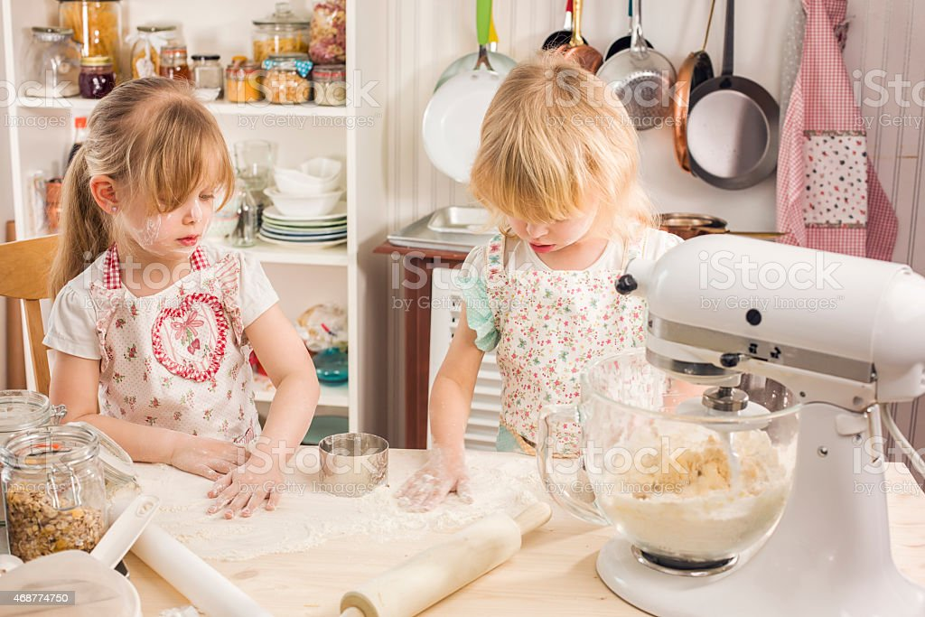 Mother and Her Daughters Preparing Cookies in the Kitchen stock photo
