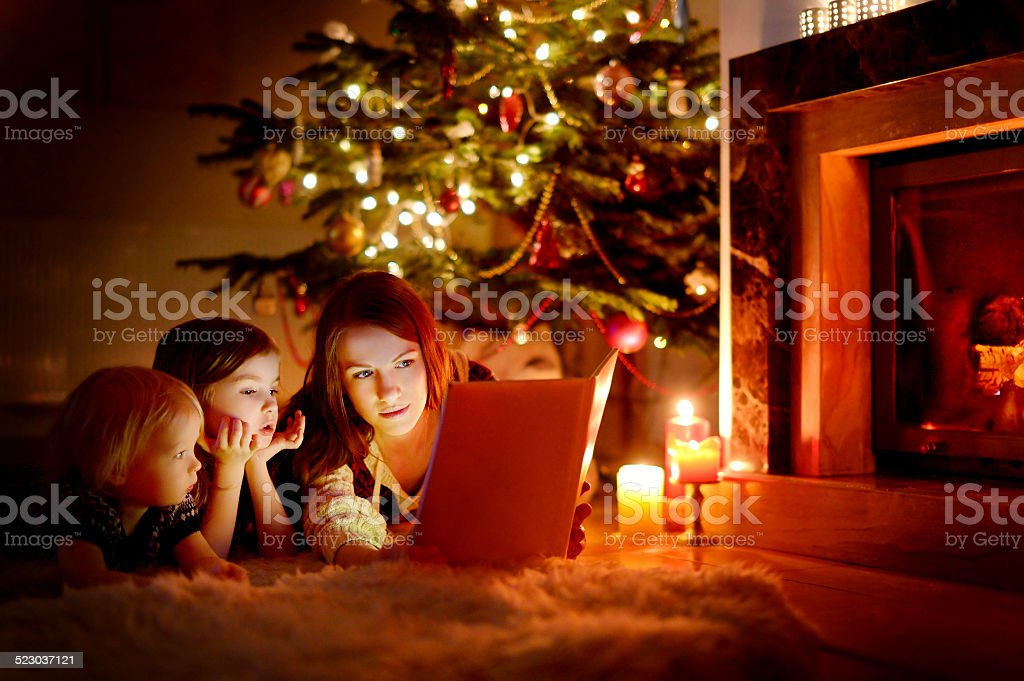 Mother and her daughters reading a book stock photo