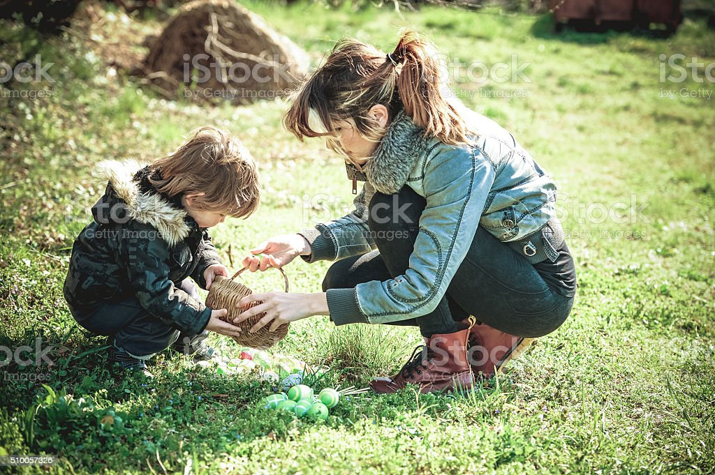 Mother and her Little Boy with Easter Eggs outdoors stock photo