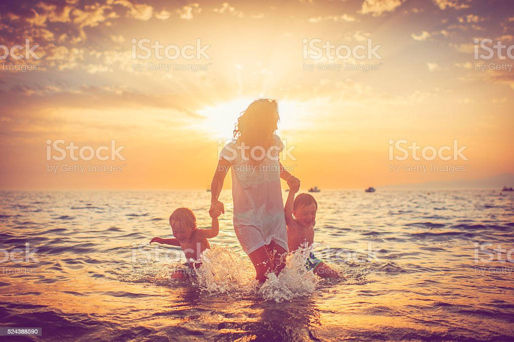 Mother and her sons by the sea stock photo