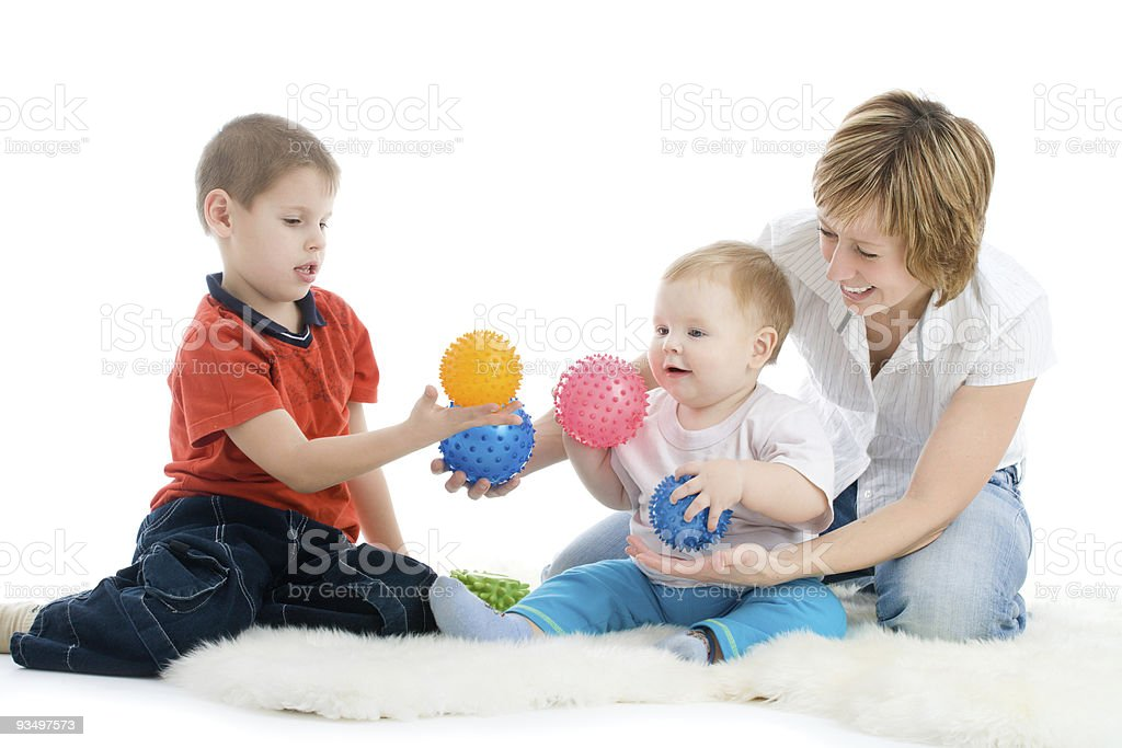 Mother and her sons enjoy with colorful balls stock photo
