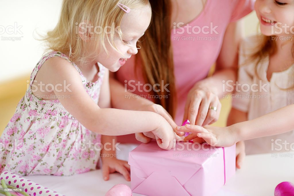 Mother and het two daughters wrapping a gift stock photo