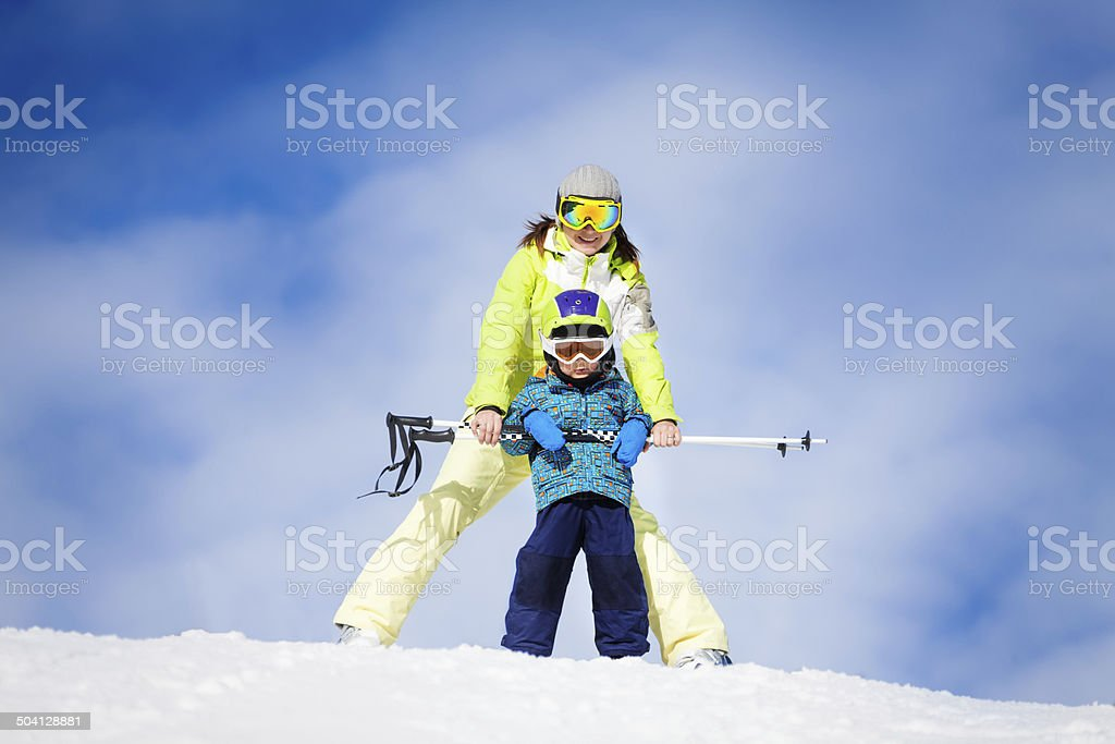 Mother and kid in masks standing with ski polls stock photo