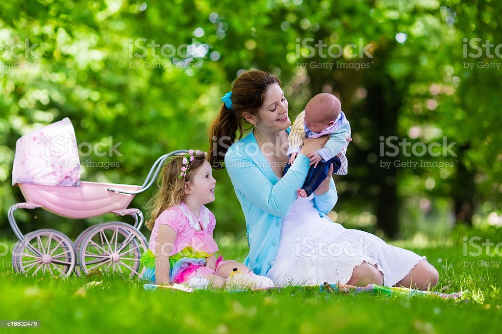 Mother and kids enjoying picnic outdoors stock photo