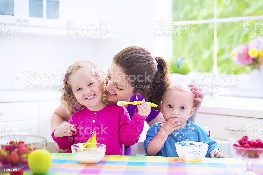 Mother and kids having breakfast stock photo