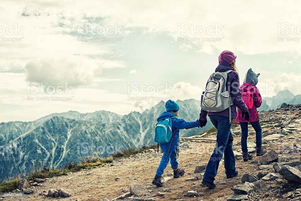 Mother and kids hiking in mountains stock photo