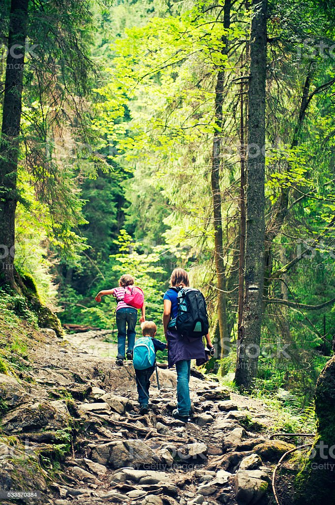 Mother and kids hiking on difficult stone path stock photo