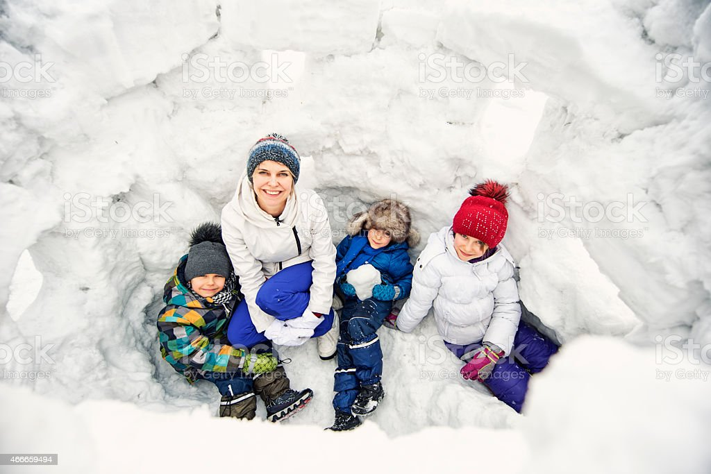 Mother and kids in a snow castle stock photo