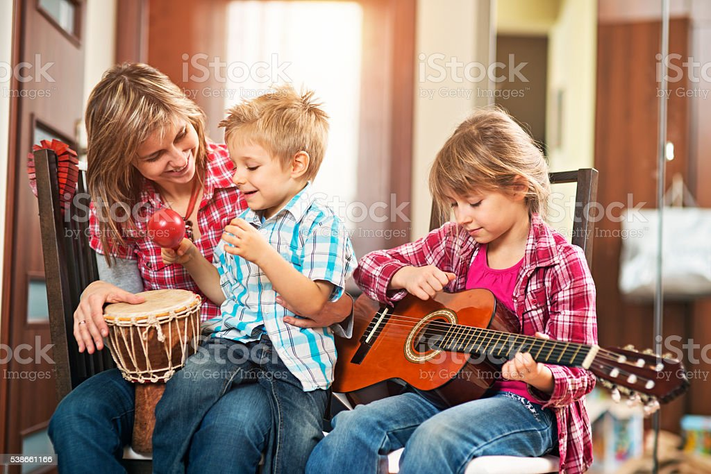Mother and kids playing music together stock photo