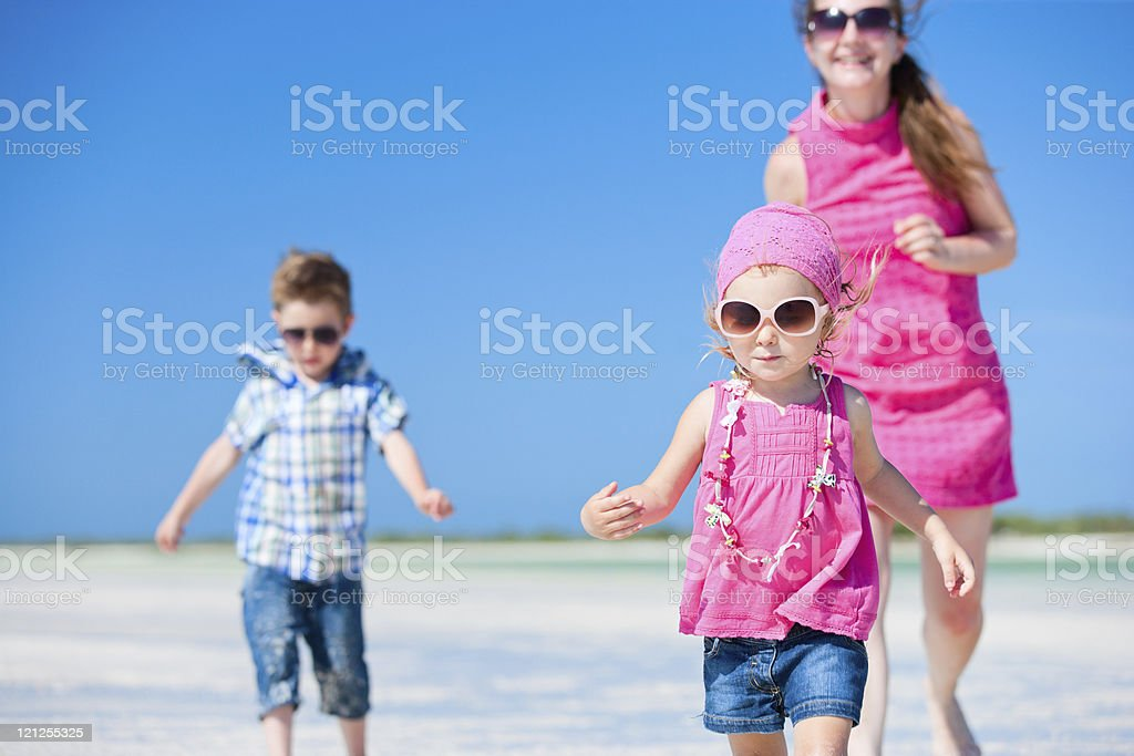 Mother and kids running at beach royalty-free stock photo
