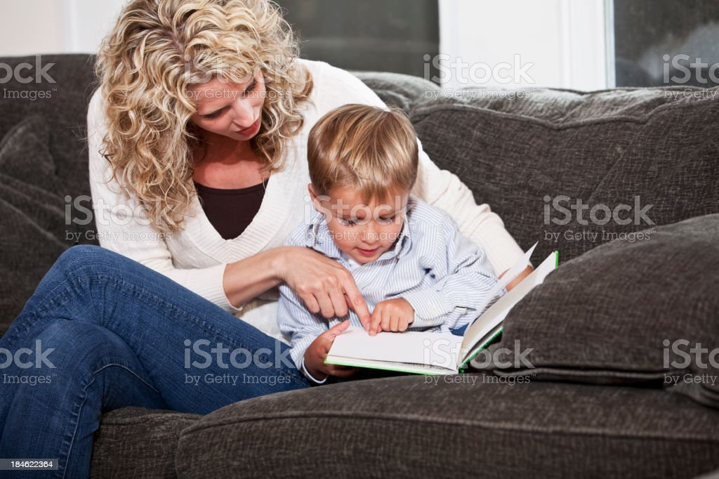 Mother and little boy reading together stock photo