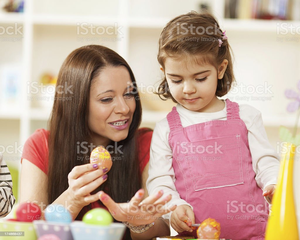 Mother and little daughter decorating Easter eggs royalty-free stock photo