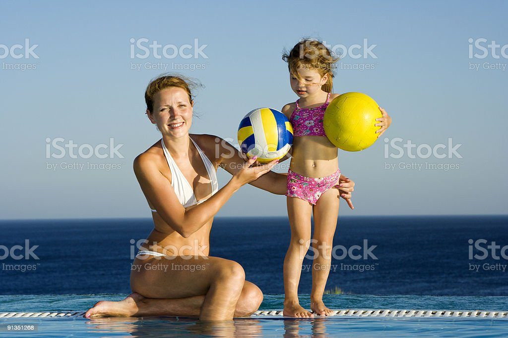 Mother and little daughter in infinity pool royalty-free stock photo
