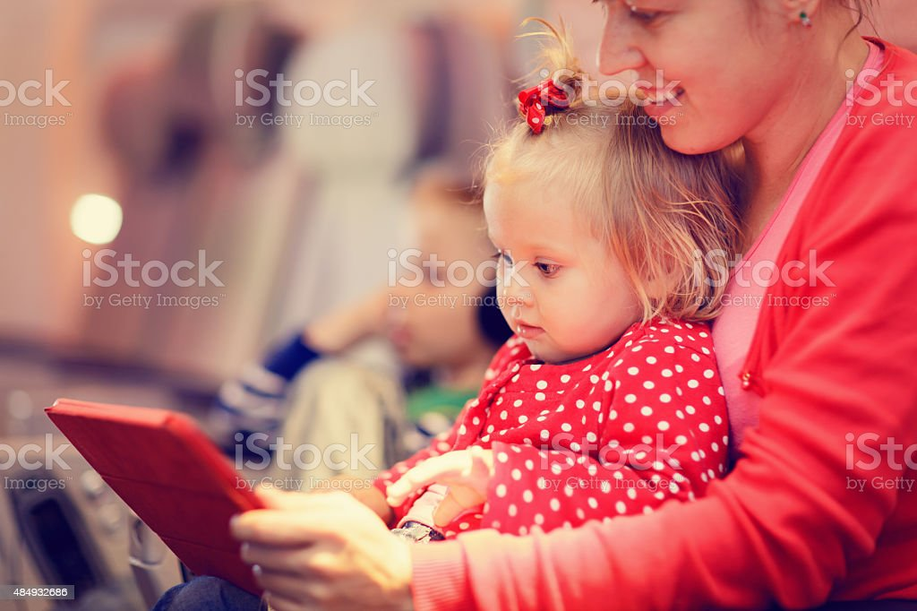 mother and little daughter looking at touch pad in plane stock photo