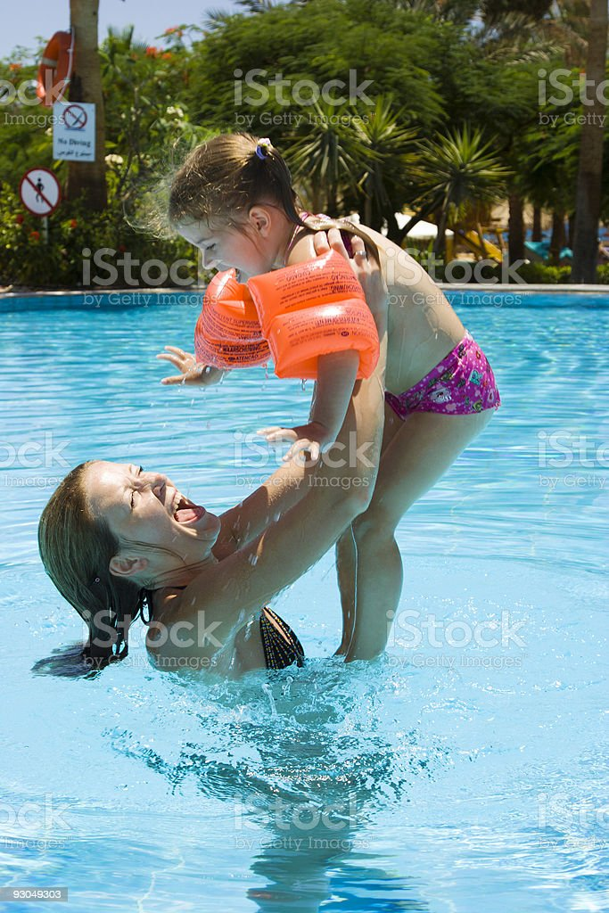 Mother and little daughter playing in pool royalty-free stock photo