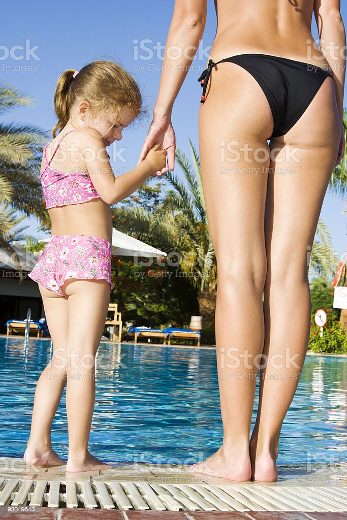 Mother and little daughter staying near pool royalty-free stock photo