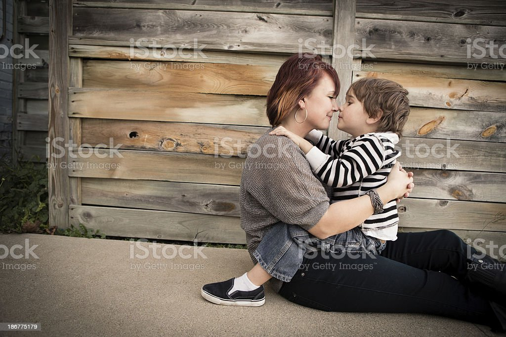 Mother and Little Son Cuddling, in Rustic, Outdoor Setting stock photo