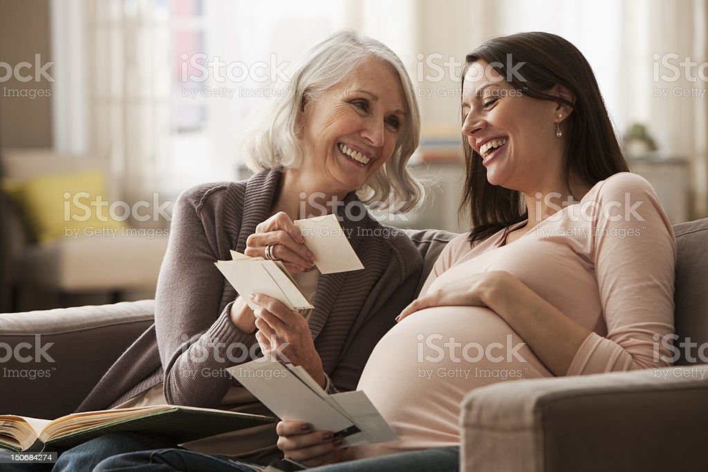 Mother and pregnant daughter sharing photographs stock photo