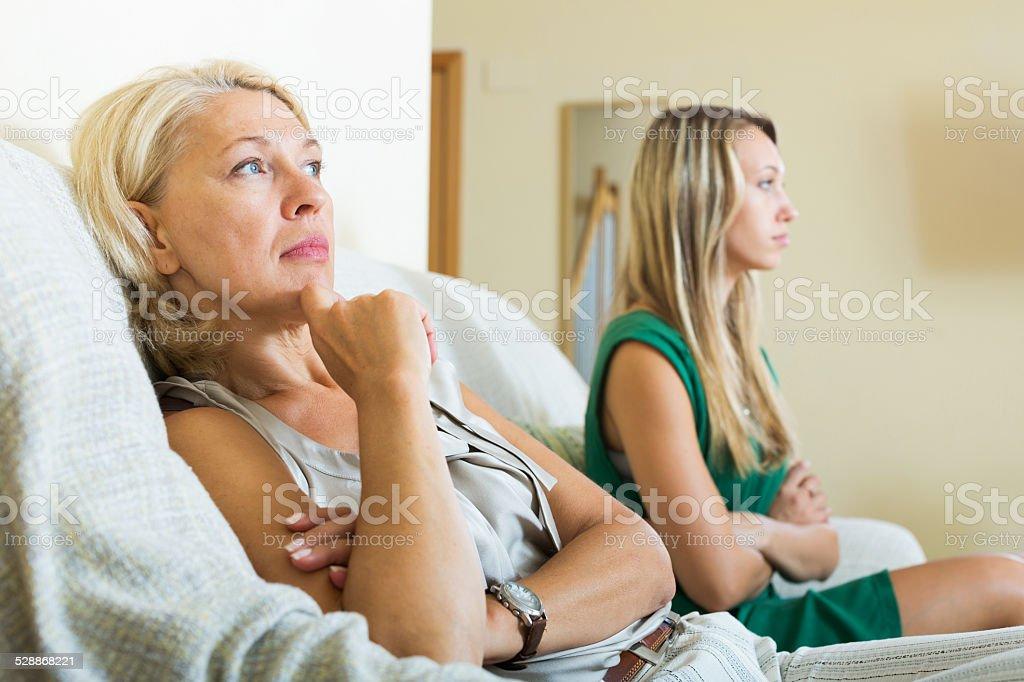 mother and sad adult daughter having quarrel stock photo