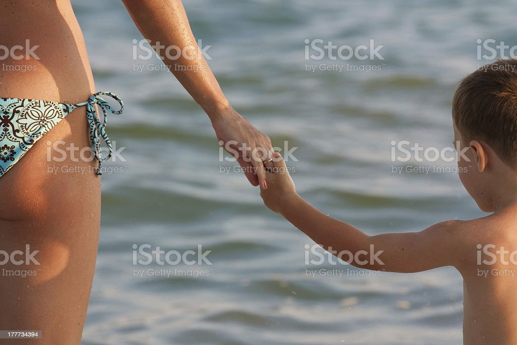 Mother and son are holding hands royalty-free stock photo