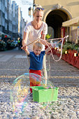 Mother and son are making huge bubbles