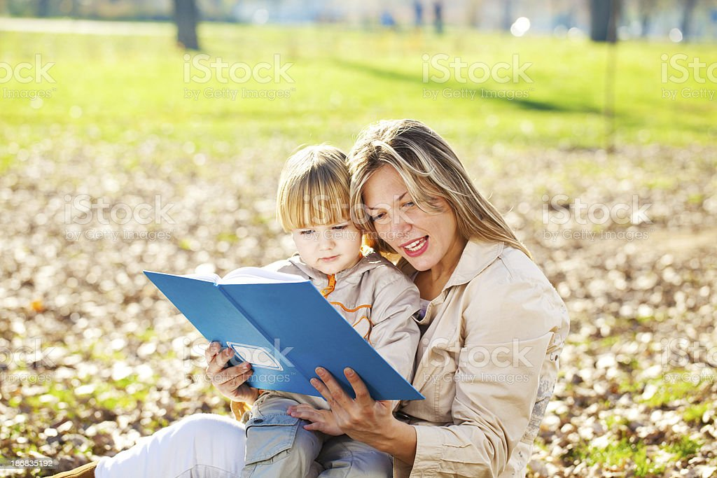 Mother and son are reading a book outdoor. royalty-free stock photo