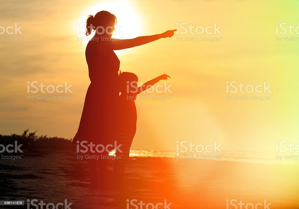 mother and son at sunset beach stock photo