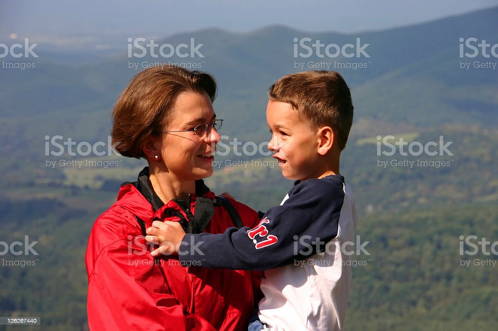 Mother and son at the top of mountain after hiking royalty-free stock photo