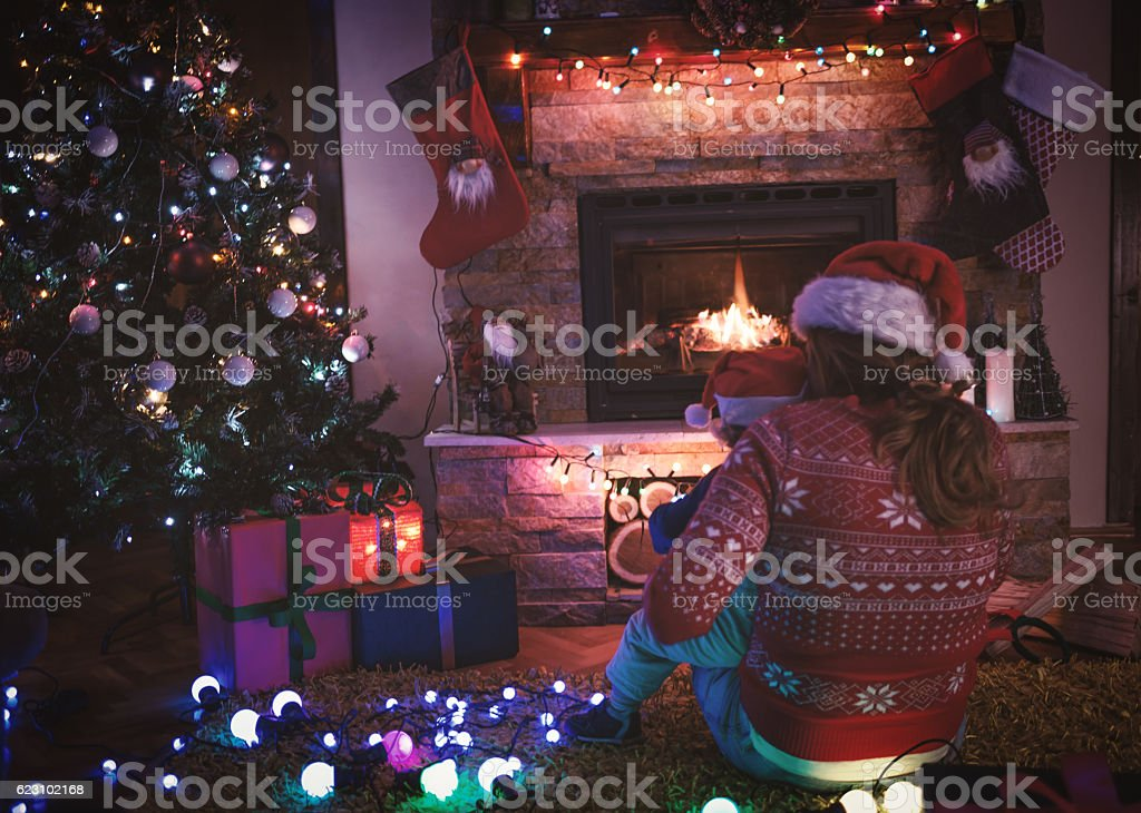 Mother and son by a fireplace on Christmas night stock photo