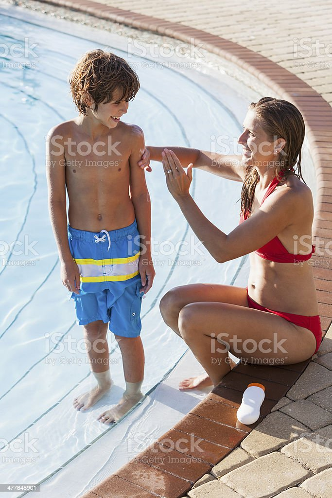 Mother and son by pool using sunscreen royalty-free stock photo